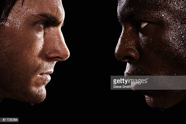 two sweaty men looking at each other in intimidation - rivaliteit stockfoto's en -beelden