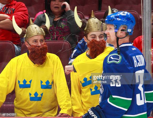 Two Swedish fans watch Henrik Sedin of the Vancouver Canucks during the warmup before their NHL game against the Pittsburgh Penguins at Rogers Arena...