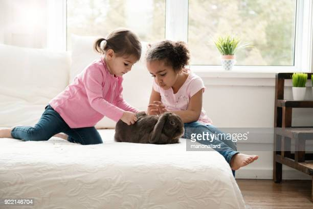 Deux fillettes sucrées s'asseoir sur le lit avec un bélier lapin mignon pendant les vacances de Pâques