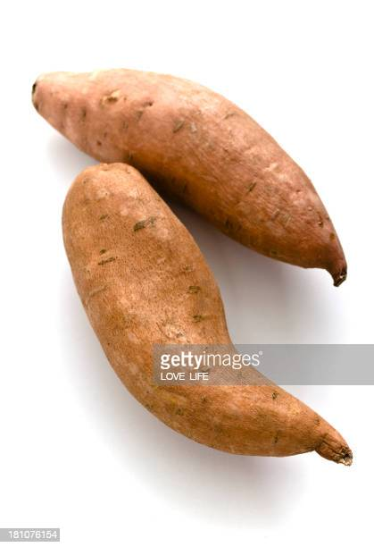 Two sweet potatoes against a white background
