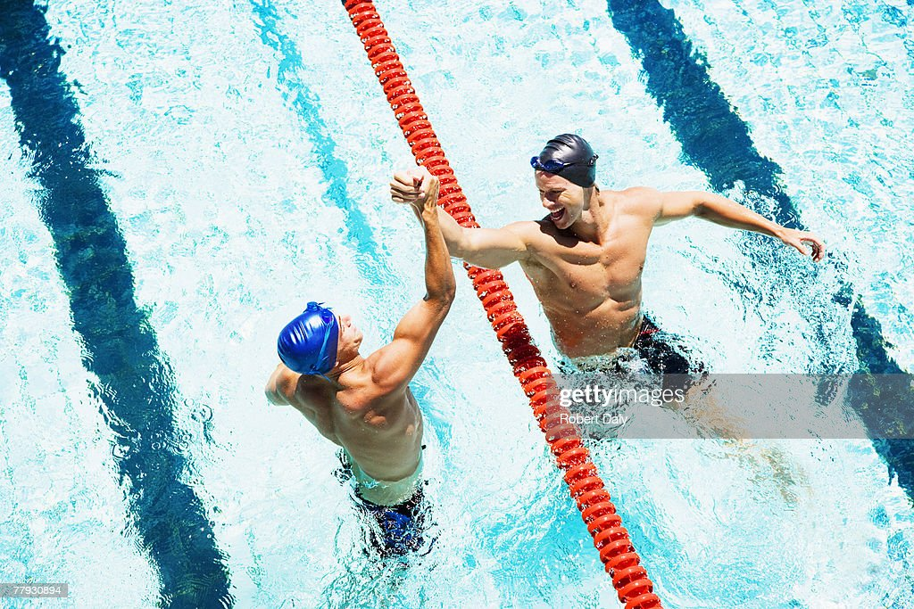 Two swimmers in a pool joining hands : Stock Photo