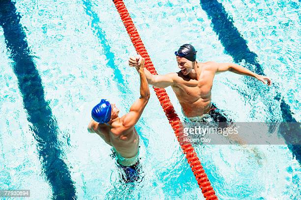 two swimmers in a pool joining hands - competitie stockfoto's en -beelden