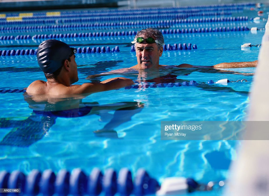Two Swimmers Talking in a Swimming Pool : Stock Photo