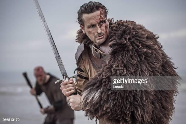 dos guerreros de sangre medieval empuñando espada que carga junto a una orilla del mar frío - hombre peludo fotografías e imágenes de stock