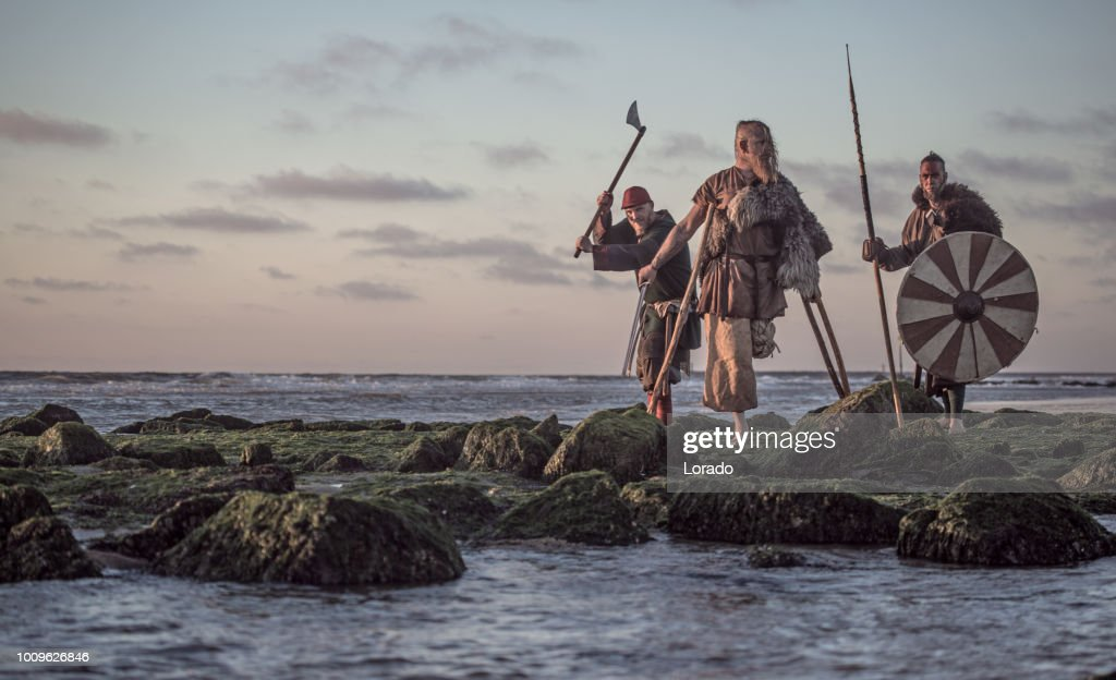 Two sword wielding bloody medieval warriors together on a cold seashore : Stock Photo