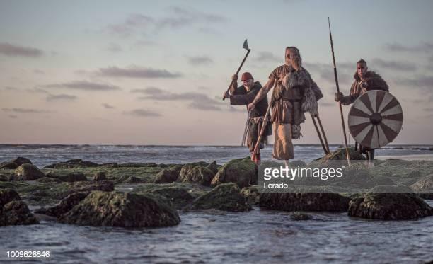 zwei schwert schwingende blutigen mittelalterliche krieger zusammen an einer kalten küste - nordeuropäischer abstammung stock-fotos und bilder