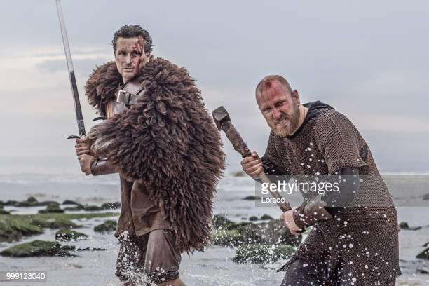 dos espada empuñando sangrientos guerreros medievales juntos a una orilla del mar frío - hombre peludo fotografías e imágenes de stock