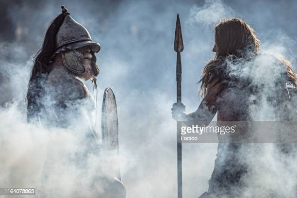 two sword wielding bloody viking warriors alone in a forest - barbarian stock photos and pictures
