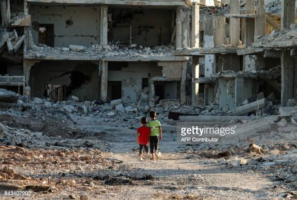 Two Syrian boys walk down a street amid destroyed buildings in a rebelheld area in the southern Syrian city of Daraa on September 6 2017 / AFP PHOTO...