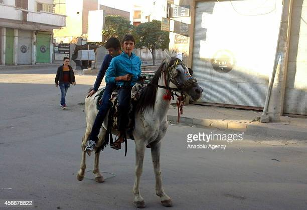 Two Syrian children ride a horse during Eid alAdha holiday in the ISIL controlled city Raqqa Syria on October 8 2014