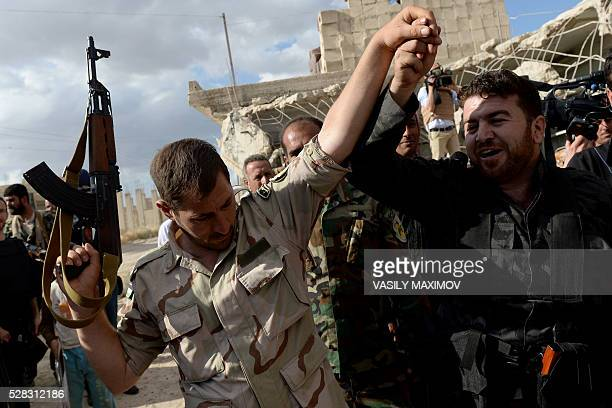 Two Syrian fighters react to the arrival of a Russian military convoy in a small village near the city of Hama on May 4 2016 Under pressure from...
