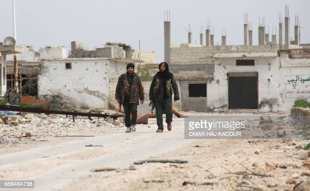 Two Syrian fighters walk in a street amidst destruction in the Syrian town of Suran in the countryside of the central province of Hama on March 22...