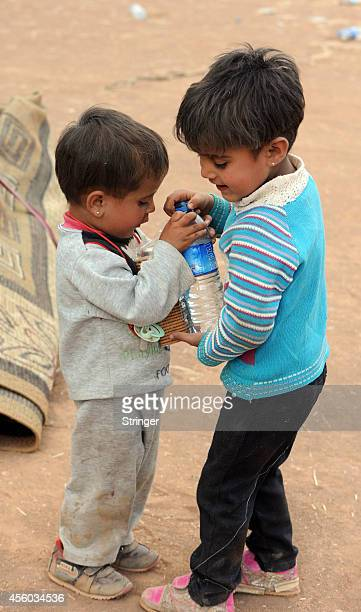Two Syrian Kurdish refugee children share a bottle of water after they enter Turkey on September 24 2014 near Suruc Turkey As many as 138000 Syrian...