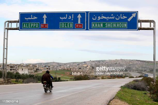 Two Syrian men drive past road signs in Khan Sheikhun on February 28, 2019. - The northwestern town of Khan Sheikhun is supposed to be protected by...