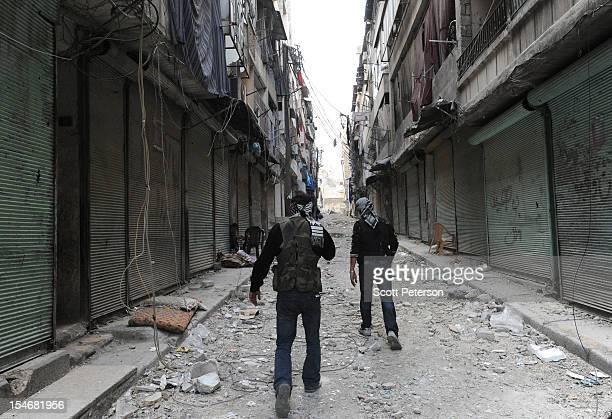 Two Syrian rebels walk up an alley in the abandoned Al Shaar district as the intense human and material cost grows from three months of intense...