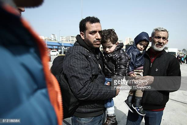 Two Syrian refugees carrying children arrive on board the Diagoras passenger ship at the port of Piraeus on March 1 2016 More than 131000 migrants...