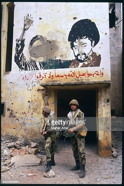 Two Syrian soldiers wearing uniforms and carrying machine guns are standing on a Beirut street beneath a mural featuring Shia cleric Mousa Sadr, and...