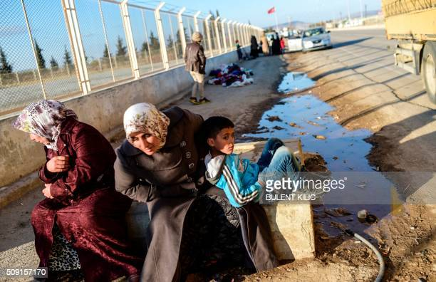 Two Syrian women and a boy wait in front of Oncupinar crossing gate near the town of Kilis to return to Syra on February 9 2016 Around 30000 Syrians...