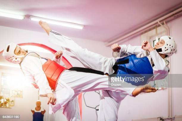 Two taekwondo fighters compete and practice high kicks with protective equipment