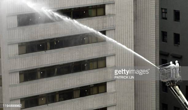 Two Taiwan firefighers clad in full protective gear spray water to disinfect a building of the Taipei Municipal Hoping Hospital on 14 May, 2003. The...