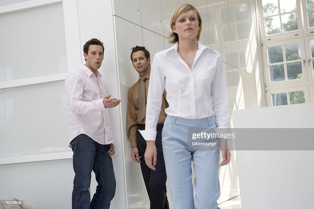 two talking behind the back of passing by woman : Stock Photo
