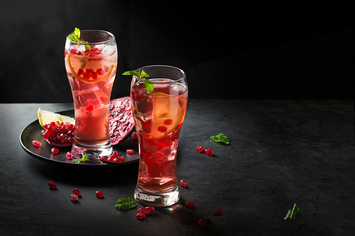 Two tall glasses of iced pomegranate juice with lemon slice on dark moody background. - gettyimageskorea