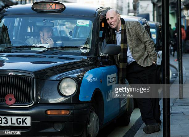 Two taxi drivers talk at a rank in St Martins Lane, London