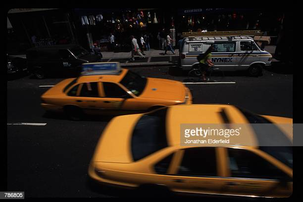 Two taxis rush by as people walk along the sidewalk June 1 1997 in New York City New York During rush hour it can take hours to get home