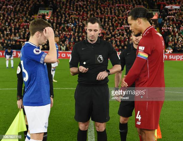 Two team captain toss the coin at the beginning of the Premier League match between Liverpool FC and Everton FC at Anfield on December 2, 2018 in...
