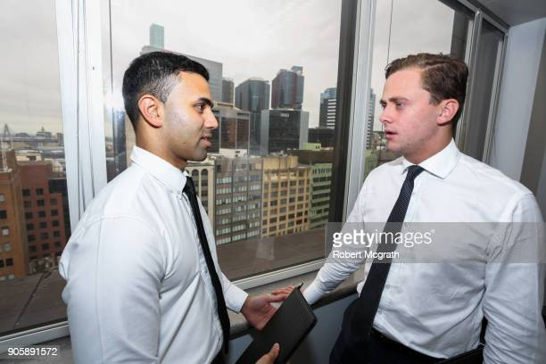 Two team members discuss options during a client meeting.