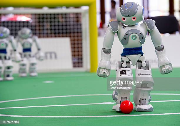 Two teams of robots play against each other in soccer at the 2013 RoboCup German Open tournament on April 26 2013 in Magdeburg Germany The robots...