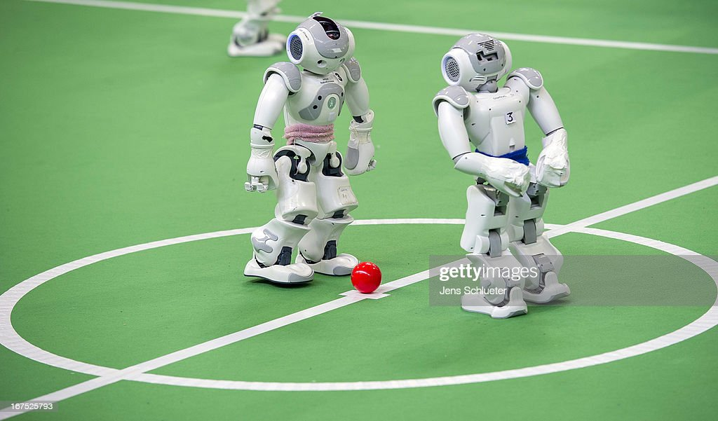 Two teams of robots play against each other in soccer at the 2013 RoboCup German Open tournament on April 26, 2013 in Magdeburg, Germany. The robots, which are a model called Nao, manufactured by Aldebaran Robotics, perform autonomously and communicate with one another via WLAN. The three-day tournament is hosting 43 international teams and 158 German junior teams that compete in a variety of disciplines, including soccer, rescue and dance.