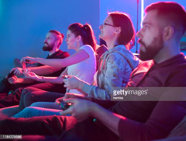 two teams playing video game in entertainment center - esport stock pictures, royalty-free photos & images