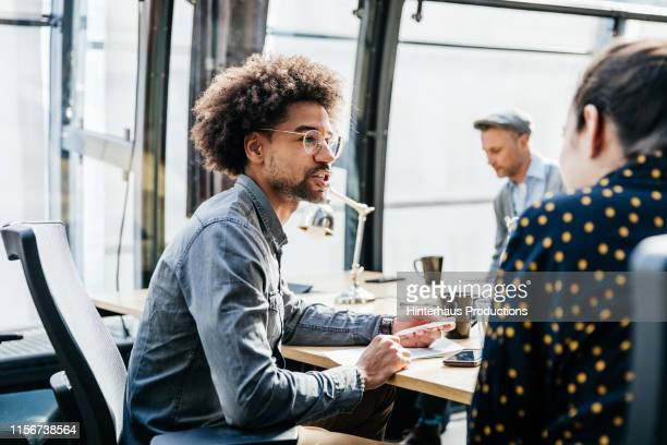 two tech startup employees talking at desk - coinvolgimento dei dipendenti foto e immagini stock