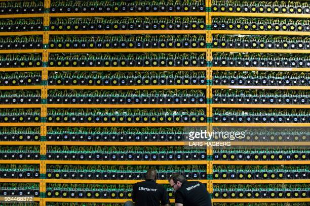 TOPSHOT Two technicians inspect bitcon mining at Bitfarms in Saint Hyacinthe Quebecon March 19 2018 Bitcoin is a cryptocurrency and worldwide payment...