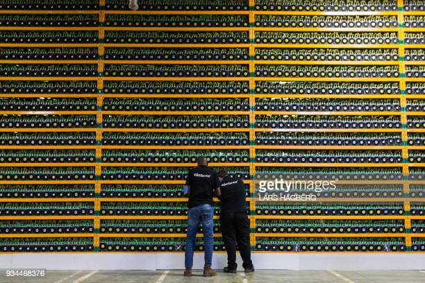 Two technicians inspect bitcon mining at Bitfarms in Saint Hyacinthe Quebecon March 19 2018 Bitcoin is a cryptocurrency and worldwide payment system...
