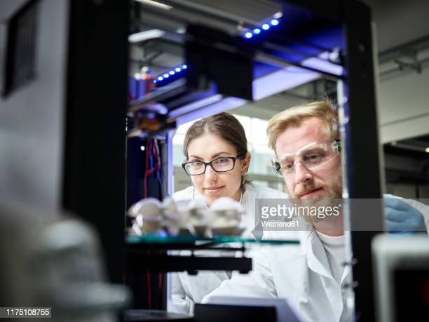 two technicians looking at turbine wheel being printed in 3d printer - 3d printing stock pictures, royalty-free photos & images