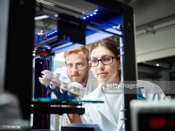 two technicians looking at turbine wheel being printed in 3d printer - verbesserung stock-fotos und bilder