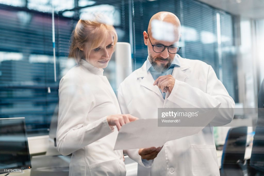 Two technicians wearing lab coats looking at plan : Stock Photo