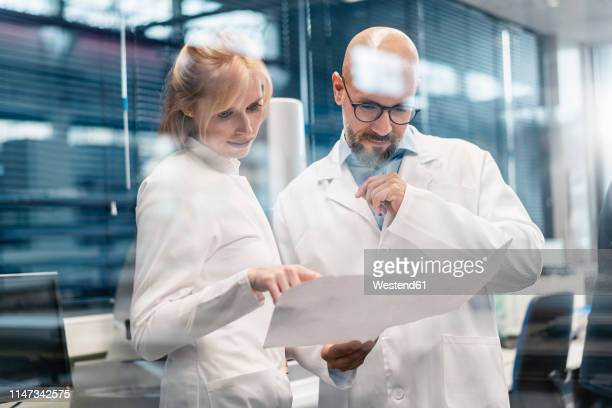 two technicians wearing lab coats looking at plan - wissenschaft stock-fotos und bilder
