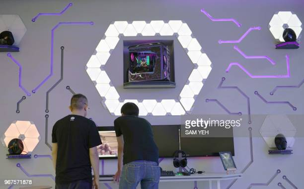 Two technicians work at the Asus music booth during Computex 2018 at the Nangang Exhibition Center in Taipei on June 5, 2018.