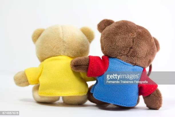 Two teddy bears hugged by friendship
