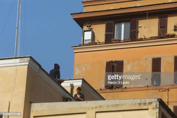 Two teen agers talk to each other on the roof of a building on March 22 2020 in Rome Italy As Italy extends its nationwide lockdown to control the...