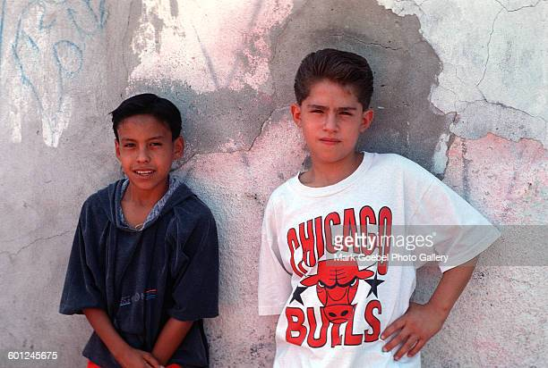 Two teen boys stand in front of a graffititagged pink and gray wall Juarez Mexico late 1980s One boy is wears a Chicago Bulls tshirt