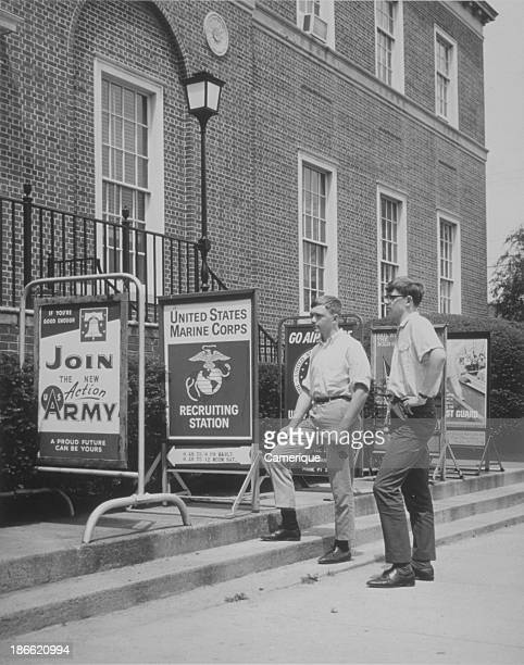 Two teen boys standing outside a military recruiting station reading signage Locustville VA June 12 1967