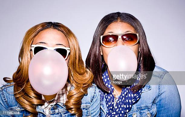 Two teen girls blowing bubbles