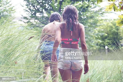 Two teen girls go exploring in tall grass
