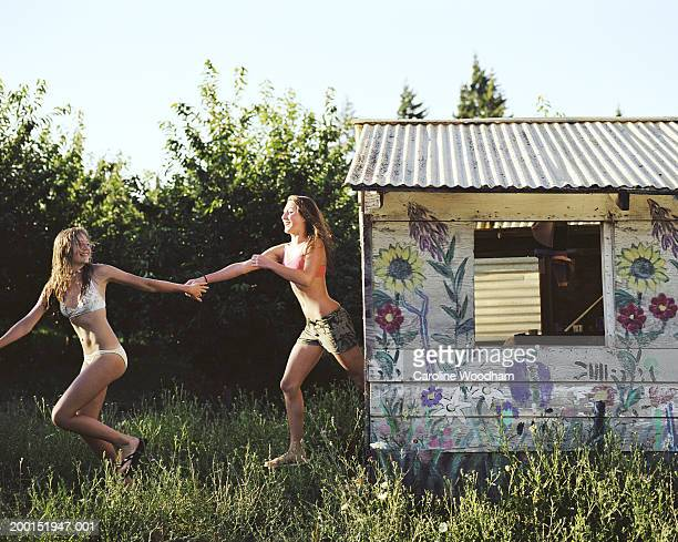 Two teen girls (13-16) holding hands, running past shed in field