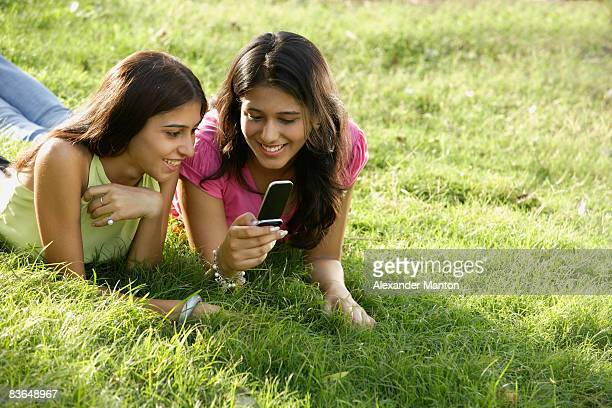 two teen girls in park, looking at text messages