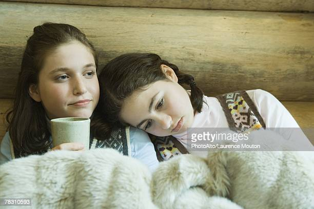 Two teen girls in winter clothes sitting under warm blanket together, one holding hot beverage